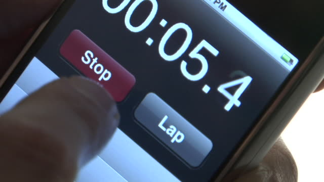 ECU, Man's finger pressing button on touch screen of mobile phone, using stop-watch function