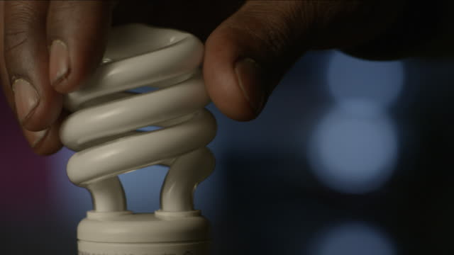 man's fingers twist a cfl light bulb in the socket, struggling to keep it on. - twisted stock videos & royalty-free footage