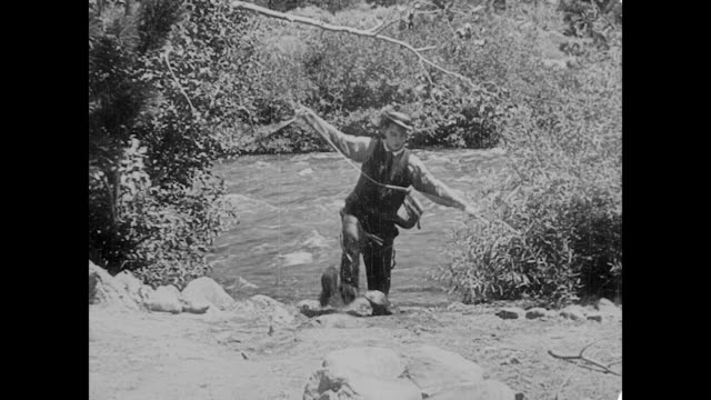 vídeos de stock, filmes e b-roll de 1923 man's (buster keaton) fishing line gets caught in tree - 1923