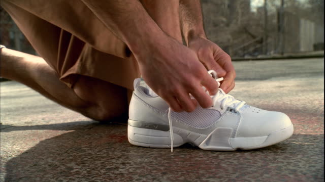 cu man's foot on basketball court as he kneels and ties the laces on his white sneaker/  harlem, new york - scarpe da ginnastica video stock e b–roll
