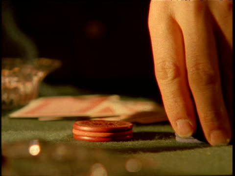 man's hand arranges piles of colourful gambling chips on card table hand of cards laid out behind - hand of cards stock videos & royalty-free footage