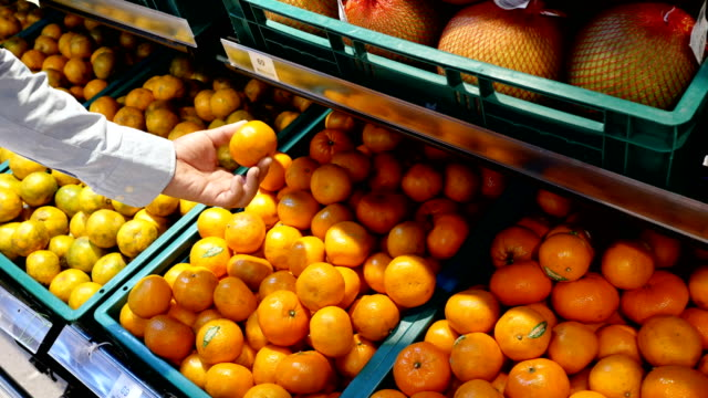 Man's hand choosing orange at the supermarket