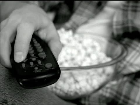 vídeos y material grabado en eventos de stock de a man's hand clicks his television remote control while he eats popcorn. - actividad móvil general