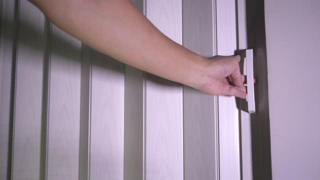 msマンの手は自宅でスライドパーティションのドアを閉める - 門点の映像素材/bロール