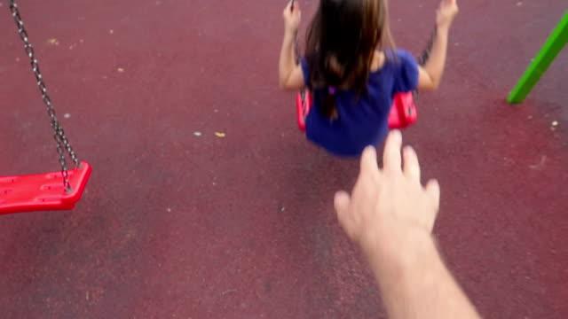 hand des mannes / vaters swing, ein kleines mädchen, kind, tochter ihren rücken auf kinderspielplatz - pushing stock-videos und b-roll-filmmaterial