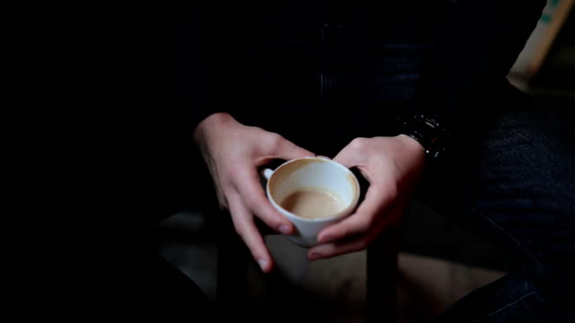 Man's hand holding a cup of coffee.