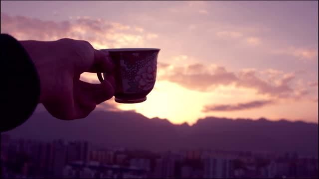 Mannens hand håller kaffekopp vid solnedgången