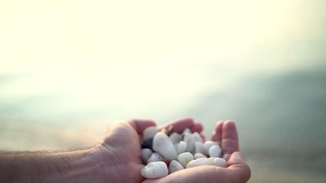 vídeos de stock, filmes e b-roll de mão do homem segurando pedras no fundo do mar. - pedra solta