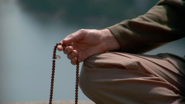 man's hand holding prayer beads / tilt up as man brings hands together in prayer position / bringing hands to third eye - prayer beads stock videos & royalty-free footage