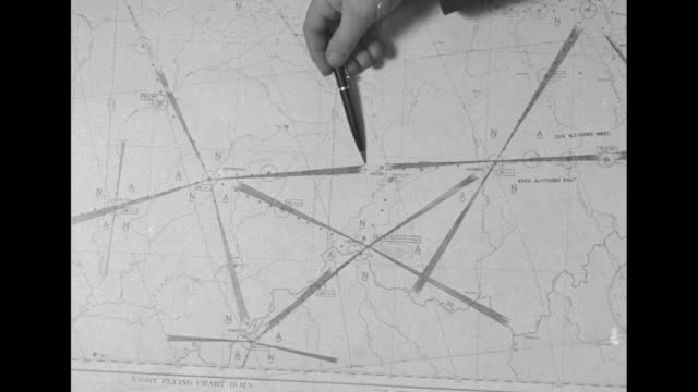 man's hand holds pen to indicate flight route on map marked night flying chart / night ms rear shot pilot in cockpit adjusting controls / passenger... - twa video stock e b–roll