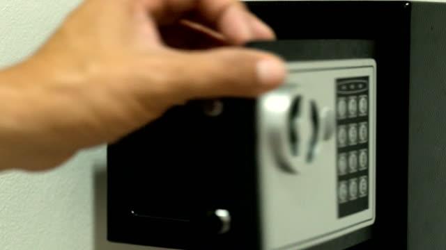 vídeos y material grabado en eventos de stock de mano del hombre en una camisa rayada abrir caja fuerte negro aislado en blanco. casa pequeña o caja fuerte del hotel. - cerradura