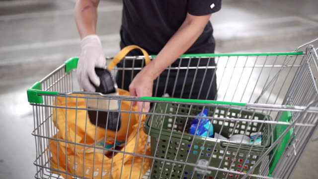 man's hand in glove picking consumer goods from a supermarket cart to reusable bag instead of plastic bags plastic bags - reusable bag stock videos & royalty-free footage