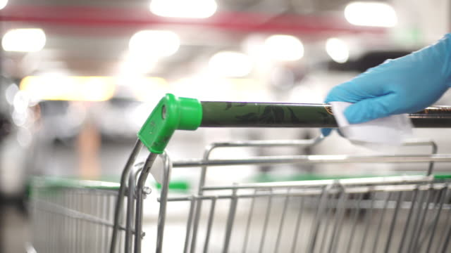 man's hand in glove wiping down door handles surfaces of the supermarket cart for cleaning curved-19 virus in the supermarket parking. - strofinare toccare video stock e b–roll