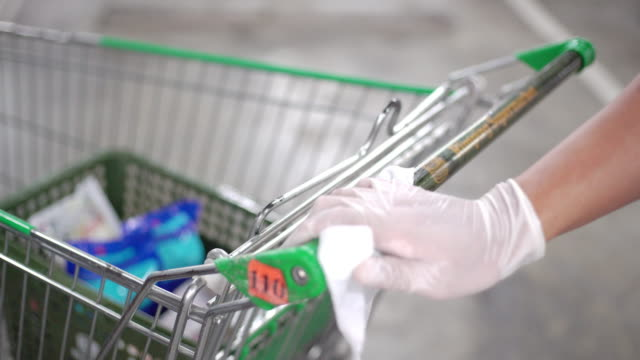 man's hand in glove wiping down door handles surfaces of the supermarket cart for cleaning curved-19 virus in the supermarket parking - cleaning glove stock videos & royalty-free footage