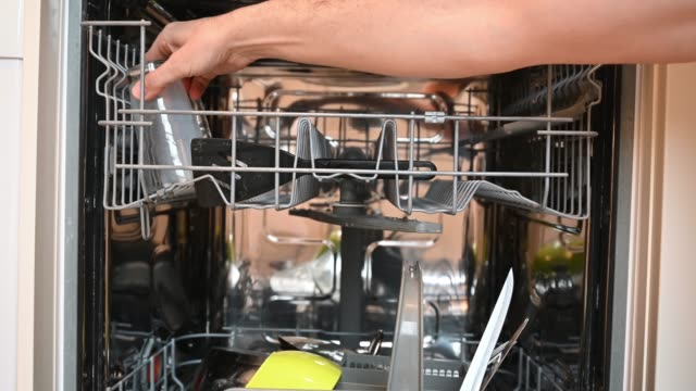vidéos et rushes de man's hand inserting a glass in the dishwasher - température