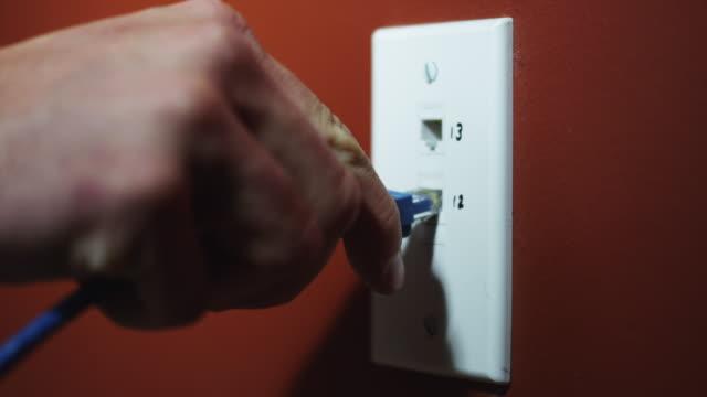 CU Man's hand inserting computer cables into socket / Orem, Utah, USA