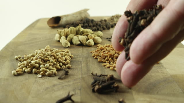 man's hand keeps cloves on a wooden board with a bunch of whole (sabut) indian masalas or spices - 密閉点の映像素材/bロール