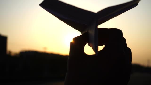 vídeos y material grabado en eventos de stock de mano del hombre de avión de papel del lanzamiento contra el sol - avión de papel