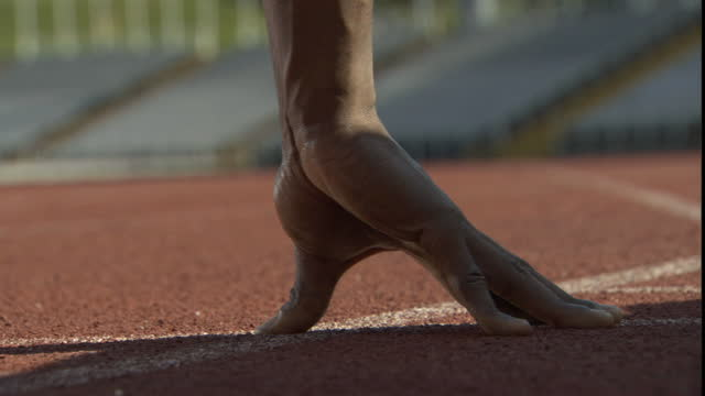 cu man's hand on track as he crouches in starting position at the beginning of a race/ sheffield, england - atletico video stock e b–roll
