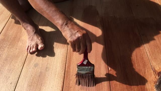 Man's hand painting wooden floor