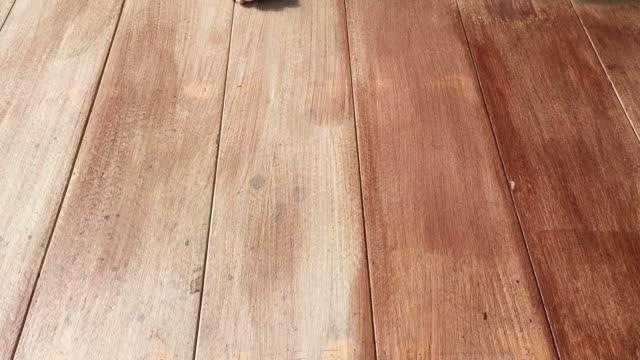 vidéos et rushes de plancher en bois de la main de peinture de l'homme - planche de bois