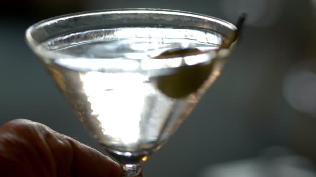a man's hand places a classic, cold refreshing martini cocktail on a table. - forbidden stock videos & royalty-free footage