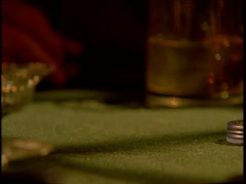 vídeos de stock e filmes b-roll de man's hand places colourful piles of gambling chips on card table - ficha de apostas