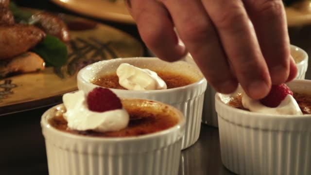 vídeos y material grabado en eventos de stock de slo mo, cu, pan, man's hand placing raspberries on whipped cream on top of creme brulee - frutas del bosque