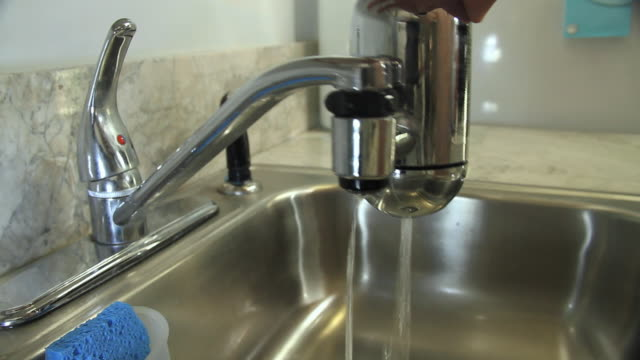 CU Man's hand pouring water from faucet with attached water filter into glass / Miami, Florida