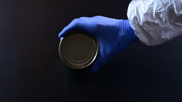 mans hand protected with plastic blue globes catching and examining a metal can. - glove stock videos & royalty-free footage