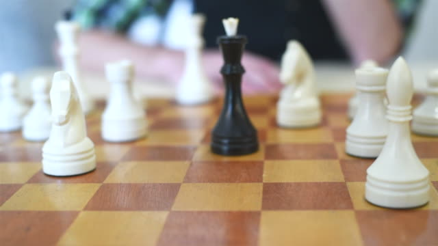 man's hand puts a white queen checkmate the black king