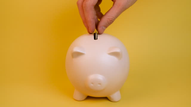 "man's hand puts coins into piggy bank - ""bbc universal"" stock videos & royalty-free footage"
