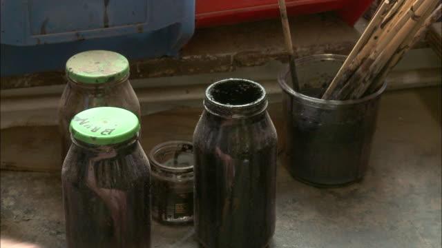cu man's hand putting cap on jar with paint / brussels, belgium - mellanstor grupp av objekt bildbanksvideor och videomaterial från bakom kulisserna