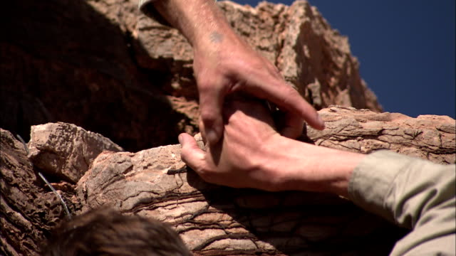 a man's hand reaches for another man hanging from a cliff. - reaching stock videos & royalty-free footage