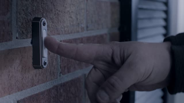 CU. Man's hand rings doorbell of brick house at night.