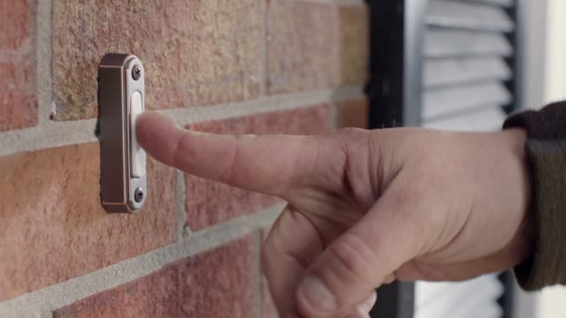 vídeos de stock, filmes e b-roll de cu. man's hand rings doorbell of brick house in the daytime. - entregador