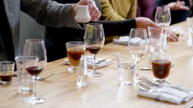 cu pan mans hand stirring sugar in coffee at table in restaurant - mittlerer teil stock-videos und b-roll-filmmaterial