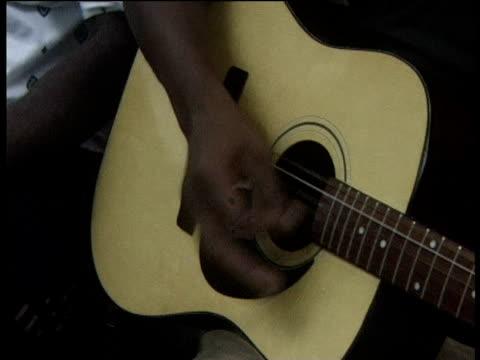 vídeos de stock, filmes e b-roll de man's hand strums guitar pan right along neck to fingers playing chords - dedilhando instrumento