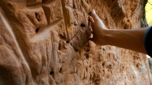 vídeos de stock, filmes e b-roll de mão do homem que toca na parede velha - rocha