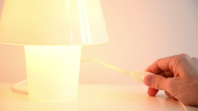 man's hand turning on and off light lamp on bedside table - electrical plug stock videos & royalty-free footage