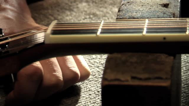 SLO MO CU PAN Mans hand turning tuning peg of acoustic guitar