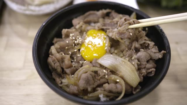 man's hand using chopsticks holds pork rice bowl with onsen tamago over plate. eating japanese food. top view shoot. - fermenting stock videos and b-roll footage