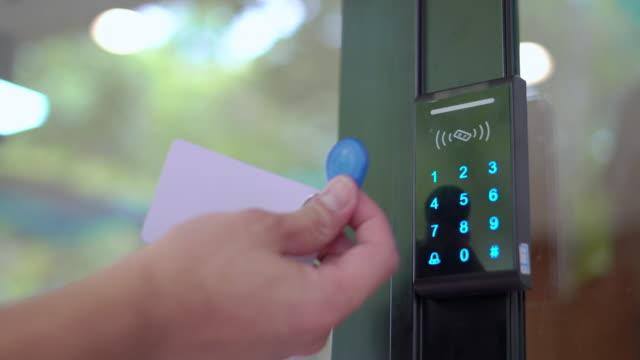mannens hand med hjälp av nyckelkortsåtkomstkontroll för att öppna och stänga dörren - byggnadskonstruktion bildbanksvideor och videomaterial från bakom kulisserna