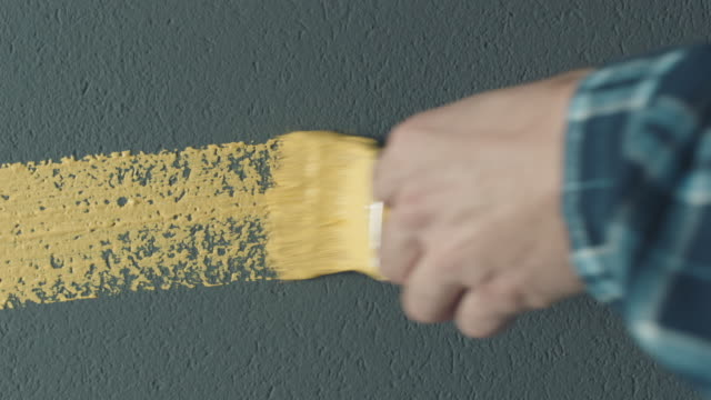 man's hand with yellow paint brush painting - painting stock videos & royalty-free footage