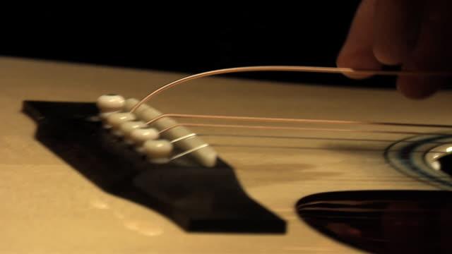 SLO MO ECU PAN Man's hands attaching acoustic guitar string