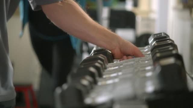 vídeos y material grabado en eventos de stock de cu, focusing, man's hands choosing dumbbell in gym, garwood, new jersey, usa - entrenamiento con pesas