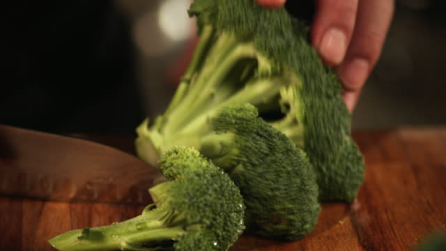 ecu, selective focus, man's hands chopping broccoli - one mature man only stock-videos und b-roll-filmmaterial
