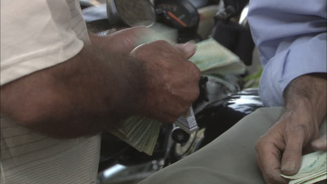 cu zi man's hands counting large stack of rials - iranian banknotes / teheran, iran - arabic script stock videos and b-roll footage