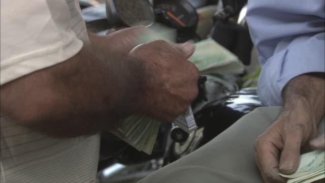 cu zi man's hands counting large stack of rials - iranian banknotes / teheran, iran - arabic script stock-videos und b-roll-filmmaterial