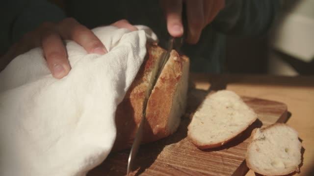 vidéos et rushes de cu man's hands cutting fresh bread with a knife. - plan de travail de cuisine